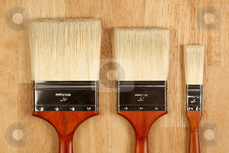 Paint Brushes on Wood Surface stock photo, Three Different Sized New Paint Brushes on a Wood Surface. by Andy Dean