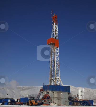Oil Rig stock photo, Drill rig with snow on the ground with blue sky by Mark Smith