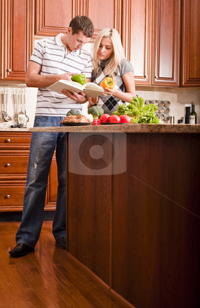 Young Couple Cooking stock photo, Young couple examine a recipe book in the kitchen. The counter is full of fresh vegetables. Vertical shot. by Christopher Nuzzaco