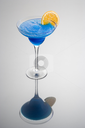 Blue Hawaiian Cocktail stock photo, Frozen Blue Hawaiian mixed drink with orange slice garnish on grey background with reflection by Gabe Palmer