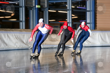 Three speed skaters stock photo, Three speed skaters making their laps on an indoor ice rink by Corepics VOF
