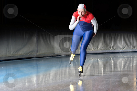 Speed skater at speed stock photo, Speed skater emerging on the straight stretch of an indoor ice rink during a long distance skating race by Corepics VOF