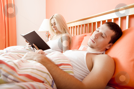 Couple Relaxing in Bed stock photo, View of couple in bed, with woman reading book and man sleeping. Horizontal format. by Christopher Nuzzaco