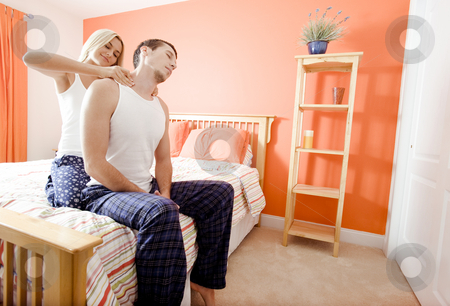 Woman Massaging Man's Shoulders in Bedroom stock photo, Man and woman sit on bed as woman massages man's shoulders. Horizontal format. by Christopher Nuzzaco