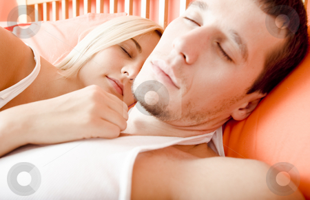 Couple Sleeping in Bed stock photo, Cropped close-up of man and woman sleeping close together in bed. Horizontal format. by Christopher Nuzzaco