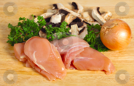 Chicken and mushroom ingredients stock photo, Ingredients for a chicken and mushroom meal, raw chicken breasts, mushrooms, onion and parsley, on a chopping board by Paul Cowan