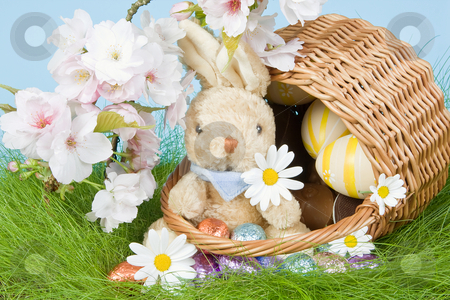 Bunny in easter basket stock photo, Easter basket with eggs and bunny in grass by Anneke