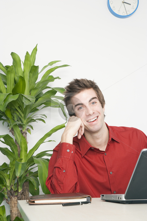 Handsome Young Businessman Smiling stock photo, Handsome young businessman rests his head on his hand as he smiles. Vertical shot. by Paul Burns
