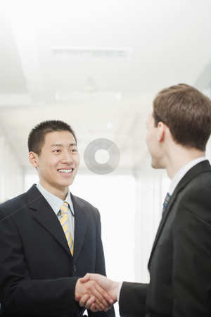 Handsome Young Businessmen Greeting stock photo, Handsome young businessmen greet each other and shake hands. Vertical shot. by Paul Burns