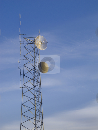 Telecommunications tower with blue sky in background stock photo, Small telecommunications mast with blue sky and white clouds in background by Marek Uliasz