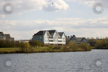 Lake houses stock photo, A lake with some wooden clad homes by Mark Bond