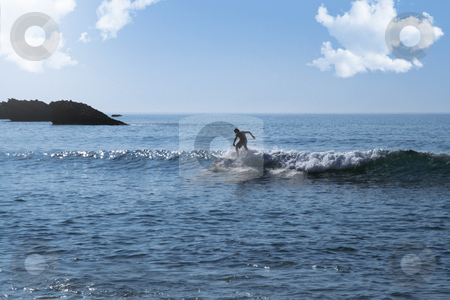 Surfer stock photo, Surfer silhouette on the ocean with rocks in background by Laurent Davoust