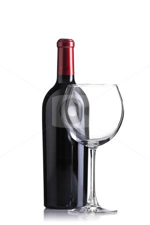 Red wine bottle and an empty glass stock photo, Isolated red wine bottle and an empty glass, focus on glass by Nikola Spasenoski