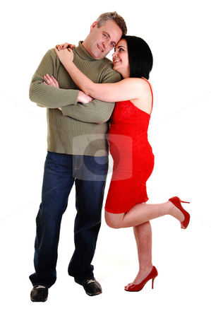 Couple hugging. stock photo, An middle age couple, she in an red dress and black hair gives her husband a big hug, standing on his side, on white background. by Horst Petzold
