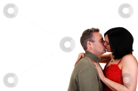 Couple kissing. stock photo, A middle age couple kissing, she in a red dress and black hair, her husband in a green sweater, with copy space on the left side, for white background. by Horst Petzold