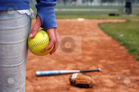 A Girl and Her Softball, Glove, and Bat stock photo, A girl holds a softball on the infield diamond. by Bryce Newell