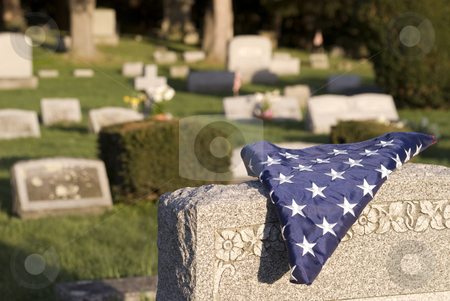 Fallen hero stock photo, A U.S. flag folded for a deceased veteran lying on a tombstone. by Christy Thompson