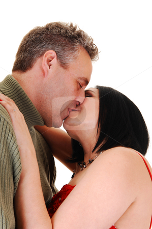Couple kissing. stock photo, A middle age couple kissing, she in a red dress and black hair, her husband in a green sweater, for white background. by Horst Petzold