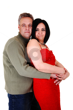 Couple hugging. stock photo, An middle age couple, she in an red dress and black hair and her husband gives her a big hug, standing on his side, on white background. by Horst Petzold