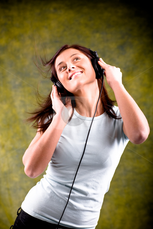 Listen to the music stock photo, Young woman listen to the music with head phones by Val Thoermer