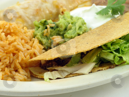 Taco with refried beans stock photo, Taco, refried beans and rice on a plate by Christy Thompson