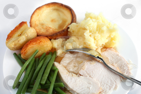 Festive turkey dinner stock photo, A festive dinner with turkey breast, green beans,  roast potatoes, mashed potatoes and yorkshire pudding. by Paul Cowan