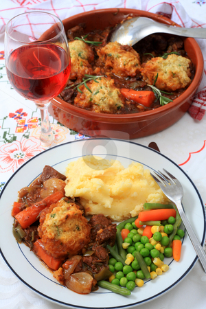 Beef stew and serving bowl vertical stock photo, A meal of beef stew with parsley dumplings, mashed potatoes and mixed vegetables with rose wine and the serving bowl behind by Paul Cowan