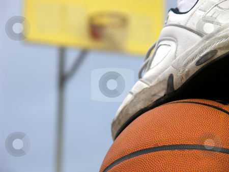 Waiting my turn stock photo, A foot on top of a basketball with out-of-focus hoop in background. by Christy Thompson