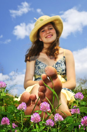 Young girl sitting on meadow stock photo, Young teenage girl sitting on summer meadow amid wildflowers in straw hat by Elena Elisseeva