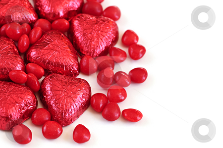Valentine candy stock photo, Red Valentine's candies and foil wrapped chocolates on white background by Elena Elisseeva