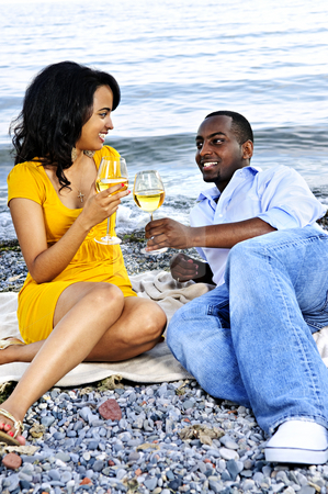Happy couple having wine on beach stock photo, Young romantic couple celebrating with wine at the beach looking at each other by Elena Elisseeva