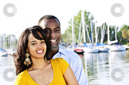 Happy couple outside stock photo, Portrait of young romantic couple standing at harbor by Elena Elisseeva
