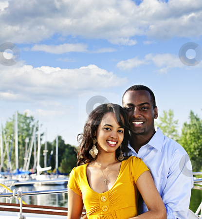 Happy couple outdoors stock photo, Portrait of young romantic couple standing at harbor with copyspace by Elena Elisseeva