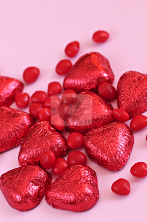 Valentine candy stock photo, Red Valentine's candies and foil wrapped chocolates on pink background by Elena Elisseeva