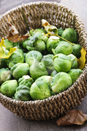 Basket of brussels sprouts stock photo, Basket of green brussels sprouts with autumn leaves by Elena Elisseeva