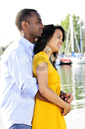 Romantic couple outdoors stock photo, Young romantic couple hugging and standing at harbor in profile by Elena Elisseeva