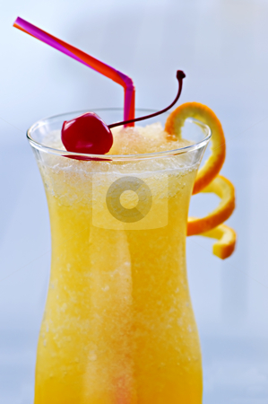 Frozen orange drink stock photo, Glass of orange juice cocktail on blue close up by Elena Elisseeva