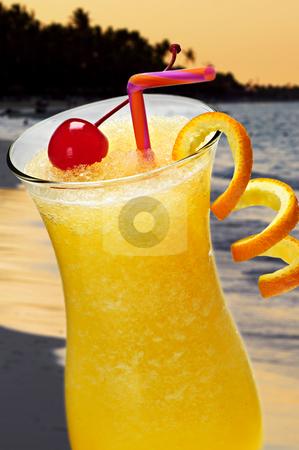 Tropical orange drink stock photo, Glass of orange juice cocktail at tropical beach by Elena Elisseeva