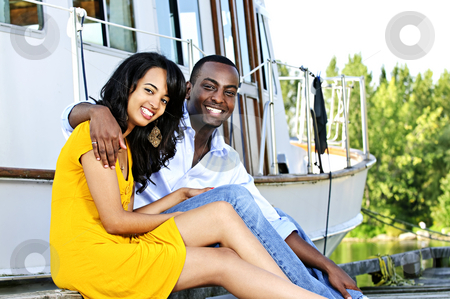 Happy couple in front of yacht stock photo, Young romantic couple sitting on dock in front of yacht by Elena Elisseeva
