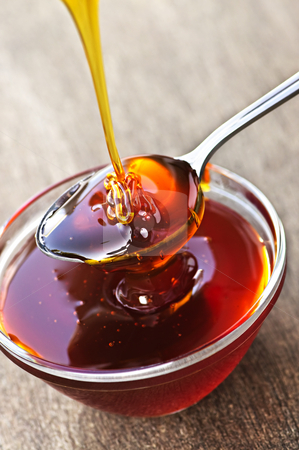 Honey dripping onto spoon stock photo, Thick golden honey drizzling onto spoon and bowl by Elena Elisseeva