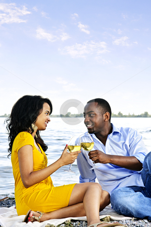 Happy couple having wine on beach stock photo, Young romantic couple celebrating with wine at the beach with copyspace by Elena Elisseeva