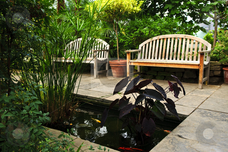Lush green garden stock photo, Lush green garden with stone landscaping, koi pond and benches by Elena Elisseeva