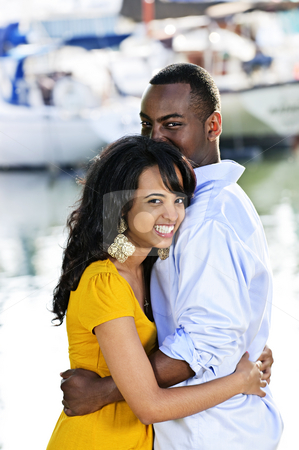 Happy couple embracing stock photo, Young romantic couple hugging and standing at harbor by Elena Elisseeva