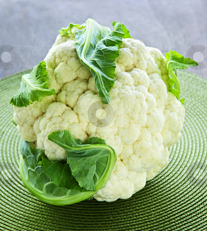 Cauliflower stock photo, Whole white organic cauliflower head with leaves by Elena Elisseeva
