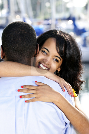 Happy woman hugging man stock photo, Portrait of beautiful young woman hugging boyfriend standing at harbor by Elena Elisseeva