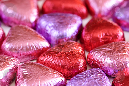 Valentine candy stock photo, Background of Valentine's chocolates wrapped in red and purple foil by Elena Elisseeva