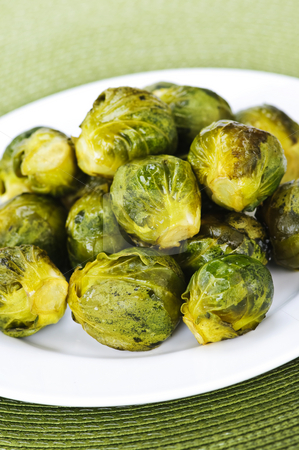 Plate of brussels sprouts stock photo, Plate of roasted green brussels sprouts on placemat by Elena Elisseeva