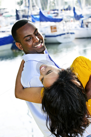 Man carrying girlfriend stock photo, Portrait of man playfully carrying his girlfriend at harbor by Elena Elisseeva