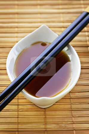 Soy sauce with chopsticks stock photo, Close up of chopsticks on white soy sauce dish by Elena Elisseeva