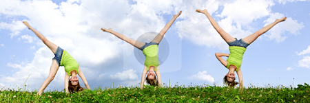 Young girl doing cartwheel stock photo, Composite image of young teenage girl doing cartwheel in a summer meadow by Elena Elisseeva